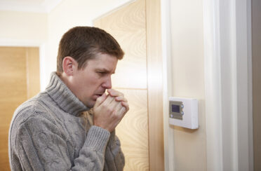 A man checks the thermostat because the furnace is blowing cold air.
